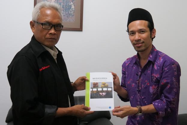 """Dr. M. Yusuf Abduh menyerahkan buku """"Dari ITB untuk Indonesia: Biorefinery Kemiri Sunan"""" kepada Rohimat selaku perwakilan dari PT. PP Bajabang Indonesia."""